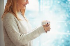 关闭拿着杯子热的可可粉或咖啡的毛线衣的美丽的少妇用蛋白软糖,当站立室内时近的窗口 库存照片