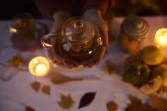 关闭拿着水壶用在黑暗后面的茶的男性手 库存图片