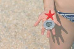 关闭拿着海星和指南针的女性手在beac 库存图片