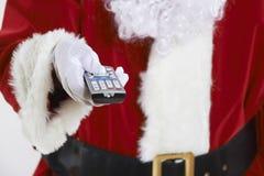 关闭拿着电视的圣诞老人遥控 免版税库存图片
