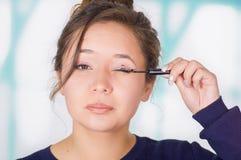 关闭拿着眼线膏和做在她的面孔的美丽的少妇疯狂的构成,在被弄脏的背景中 免版税库存照片