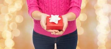 关闭拿着礼物盒的桃红色毛线衣的妇女 库存照片