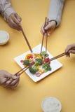 关闭拿着筷子和分享一个盘的人 库存照片