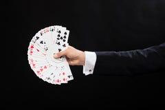 关闭拿着纸牌的魔术师手 免版税库存图片