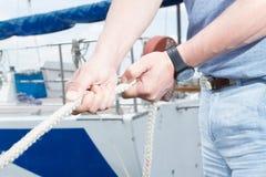 关闭拿着绳索的人手 绳索特写镜头在驾游艇者手上 白色绳索和黑手表 免版税库存图片