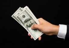 关闭拿着美元现金金钱的男性手 免版税图库摄影