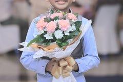 关闭拿着花的美丽的花束快乐的亚裔男孩 儿童甜华伦泰` s天概念 葡萄酒口气 免版税库存照片