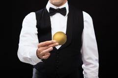 关闭拿着金黄硬币的赌博娱乐场经销商 免版税库存图片