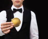 关闭拿着金黄硬币的赌博娱乐场经销商 库存照片