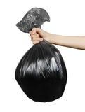 关闭拿着黑垃圾袋的人手 查出在白色 免版税库存图片