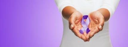 关闭拿着紫色了悟丝带的手 库存照片