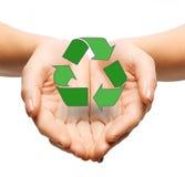 关闭拿着绿色回收的标志的手 免版税库存照片