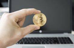 关闭拿着bitcoin的一枚金黄硬币人` s手的图象反对一台膝上型计算机在背景中 Bitcoin隐藏 免版税库存照片