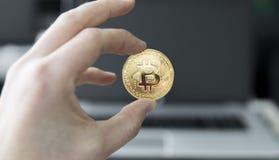 关闭拿着bitcoin的一枚金黄硬币人` s手的图象反对一台膝上型计算机在背景中 Bitcoin隐藏 库存照片