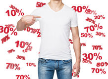 关闭指出对胸口折扣和销售的概念牛仔布的人和一件白色T恤杉 10% 20% 30% 50% 库存照片