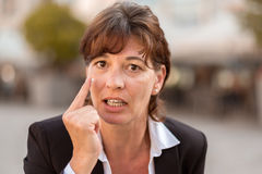 关闭指向她的手指的恼怒的女实业家 库存图片