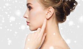 关闭指向手指的妇女在雪的耳朵 库存照片