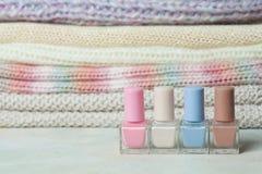 关闭指甲油和被编织的sweates在背景 淡色,秀丽时尚冬天概念 库存照片