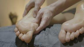 关闭按摩脚趾和一个皮包骨头的白人妇女的脚的男性手在一个松弛温泉中心- 股票录像