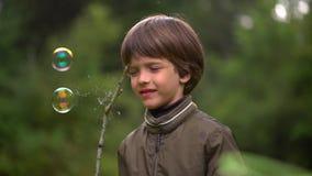 关闭捉住肥皂泡一个非常逗人喜爱的年轻男孩的画象 慢动作 股票视频