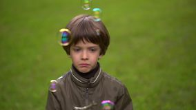 关闭捉住肥皂泡一个非常逗人喜爱的年轻男孩的画象 慢动作 股票录像