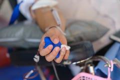 关闭接受血液和在手中拿着橡胶球的亚洲男性的右臂 医疗保健和慈善 图库摄影