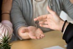 关闭接受钥匙的夫妇对新的家 免版税库存图片