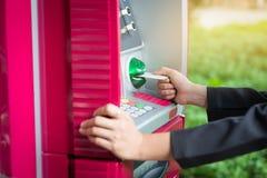 关闭插入卡片的妇女手入ATM 插入信用加州 免版税库存图片