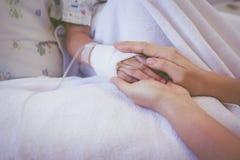 关闭握孩子的手的父母的手在医院 减速火箭 库存图片