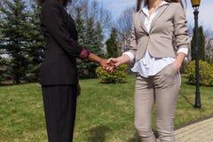 关闭握手的两名女实业家射击  妇女常设外部和佩带的企业衣裳 库存照片
