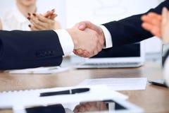 关闭握手的商人在会议或交涉上在办公室 伙伴是满意的,因为 库存图片