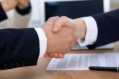 关闭握手的商人在会议或交涉上在办公室 伙伴是满意的,因为 免版税库存图片