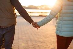 关闭握手的年轻爱恋的夫妇后面看法  有婴孩摇篮车的父母在秋天公园 爱,父母身分,家庭,晒干a 库存照片