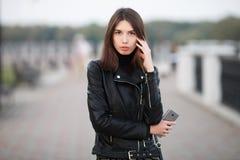 关闭摆在全长户外城市公园的一名年轻俏丽的深色的妇女的情感画象佩带黑皮革外套举行 免版税图库摄影