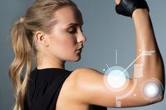关闭摆在和显示二头肌的妇女在健身房 图库摄影