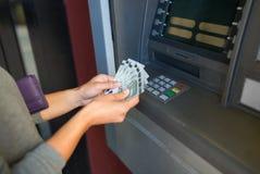 关闭撤出金钱的手在atm机器 免版税库存图片
