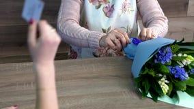 关闭支付花花束的顾客使用在花店的信用卡 股票视频