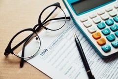 关闭收入税单计划, 1040报税表,与计算器、笔和眼睛木桌的玻璃地方 库存图片