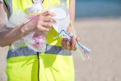 关闭收集塑料废物的人从被污染的海滩 库存图片