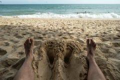 关闭放松在一个热带海滩的一个人脚在海附近 图库摄影