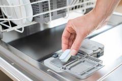 关闭放洗涤剂片剂的妇女入洗碗的水 免版税库存图片