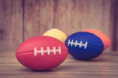 关闭放置在与其他颜色橄榄球球玩具的木地板的孩子的红色橄榄球球玩具在背景中 图库摄影