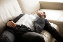 关闭放置在长沙发的被用尽的商人 库存图片