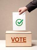 关闭放表决的男性手入投票箱 图库摄影