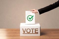 关闭放表决的男性手入投票箱 免版税库存照片