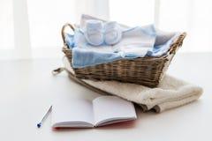 关闭新出生和笔记本的婴孩衣裳 库存图片