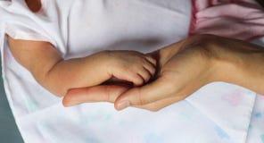 关闭新出生的手和手指和母亲,选择聚焦, f 库存照片