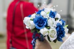 关闭新娘举行的蓝色和白色婚礼花束 免版税图库摄影