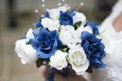 关闭新娘举行的蓝色和白色婚礼花束 免版税库存照片