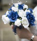 关闭新娘举行的蓝色和白色婚礼花束 库存图片
